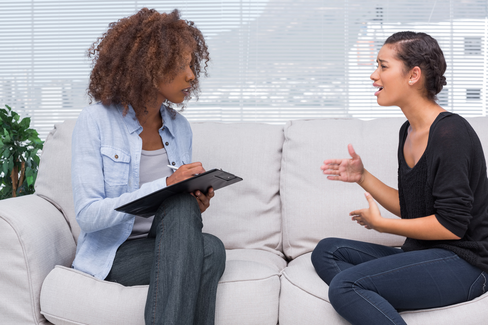 Woman gesturing and speaking to her therapist who is taking notes
